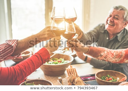 happy senior woman with glass of red wine at home stock photo © dolgachov