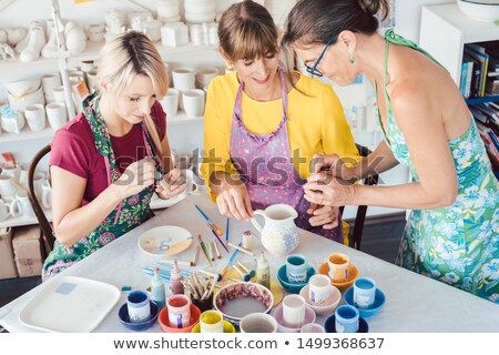 Two women painting own ceramic tableware in DIY workshop Stock photo © Kzenon