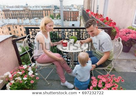 Happy family having breakfast on the balcony. Breakfast table with coffee fruit and bread croisant o ストックフォト © galitskaya