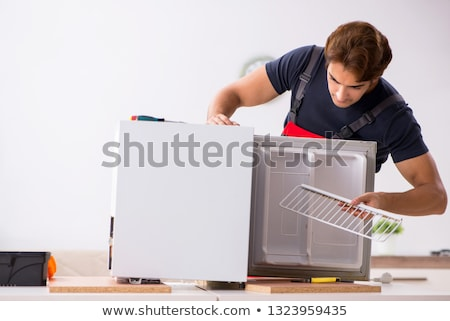 Stock photo: Young handsome contractor repairing fridge