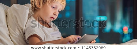 The boy uses the tablet in his bed before going to sleep on a background of a night city. Children a Stock photo © galitskaya