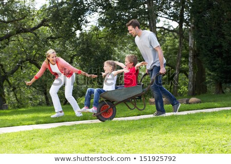 Parents Giving Children Ride In Wheelbarrow Stock photo © monkey_business