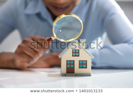 businesswoman holding magnifying glass over house model stock photo © andreypopov