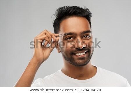 indian man with tweezers tweezing eyebrow hair Stock photo © dolgachov