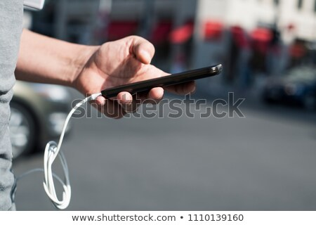 man using smpartphone with a cable plugged into it Stock photo © nito