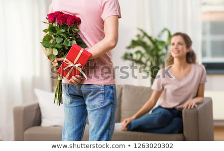 woman looking at man with bunch of flowers at home Stock photo © dolgachov