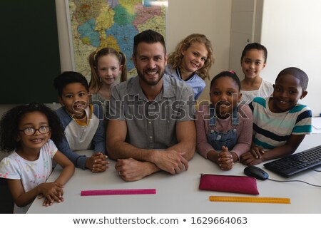 Front view of happy female teacher and schoolkids looking at camera while studying at table in schoo Stock photo © wavebreak_media