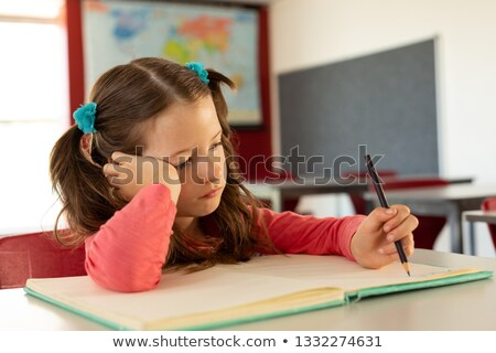 Front view of sad pretty Caucasian girl writing on notebook in a classroom at elementary school Stock photo © wavebreak_media