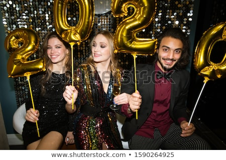 Happy young friends holding golden inflatable numbers of the following year Stock photo © pressmaster