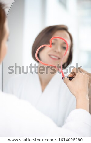Reflection of young flirty woman drawing heart with crimson lipstick on mirror Stock photo © pressmaster
