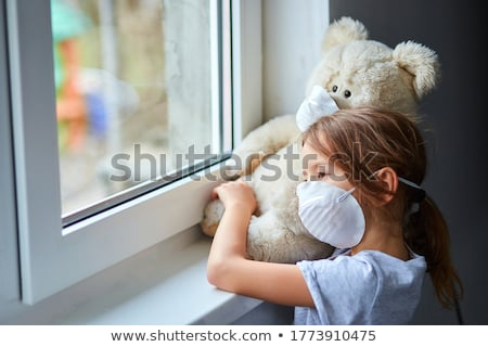 Little girl holding and hugging teddy bear in mask near the window. Stock photo © Illia