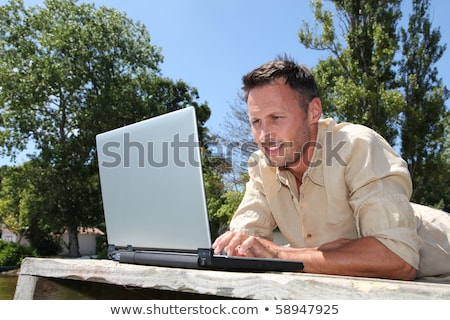 Stock photo: man on a pontoon using computer