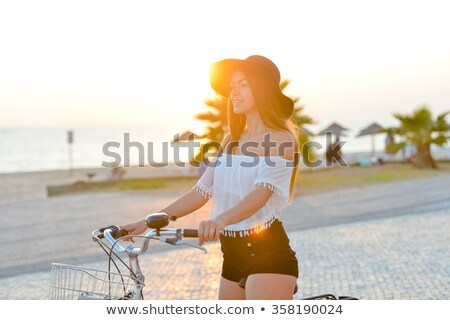 woman on a bicycle wearing a hat stock photo © photography33