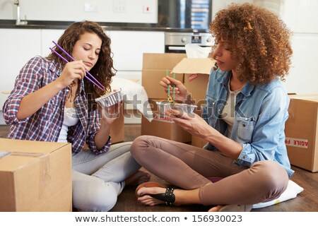 two female friends enjoying chinese takeaway meal at home stock photo © monkey_business
