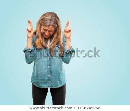 Mature woman wishing with crossing fingers Stock photo © bmonteny