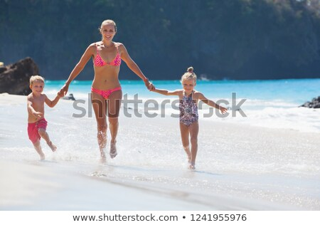 Happy family with little girl splashes feet water on beach in ev Stock photo © Paha_L