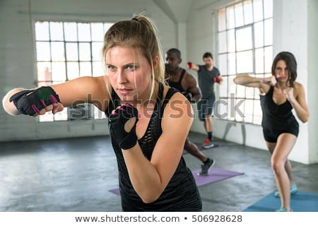 Trainer assisting woman in boxing Stock photo © wavebreak_media
