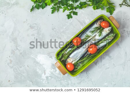 Sardines or baltic herring with thyme on green dish, flat lay Stock photo © artsvitlyna