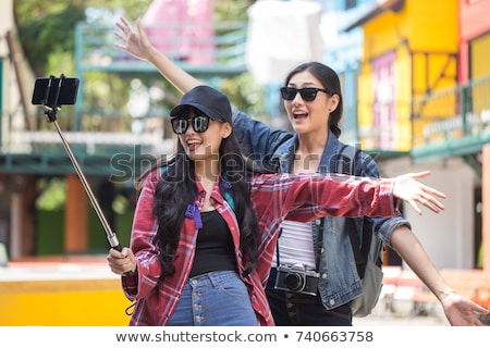 Photo of two young women traveling abroad together, and using mo Stock photo © deandrobot