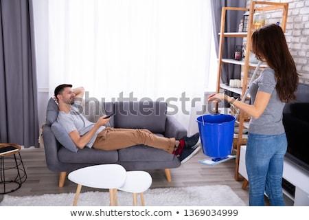 Frau halten Eimer stehen faul Mann Stock foto © AndreyPopov