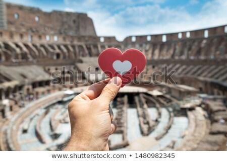 man holding heart shape inside of colosseum stock photo © andreypopov