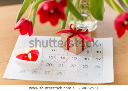 gift box, calendar sheet and flowers on table Stock photo © dolgachov