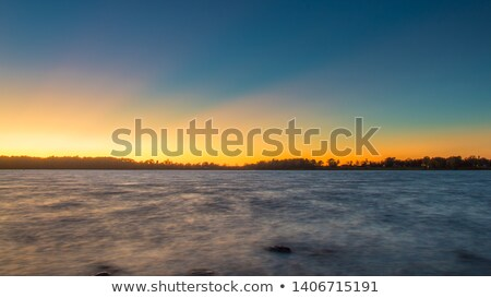 Sunrays and dark clouds over frozen lake Stock photo © Mps197