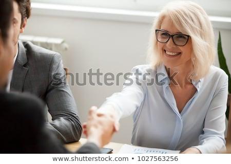 senior · mulher · amigável · aperto · de · mão · sorridente · saudação - foto stock © Edbockstock