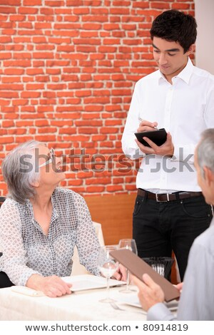 young waiter serving an older couple in a restaurant stock photo © photography33