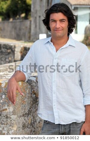 Man with long hair leaning on an old stone wall Stock photo © photography33