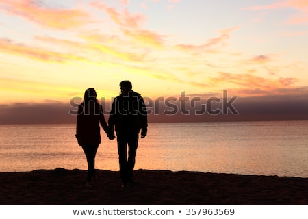 Young boy and girl look at each other, hand in hand on beach stock photo © Kotenko