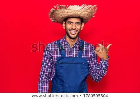 Man wearing a hat and apron pointing away stock photo © stockyimages