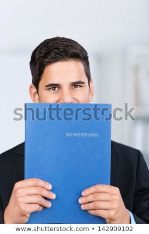 Smiling man hiding behind a folder Stock photo © photography33