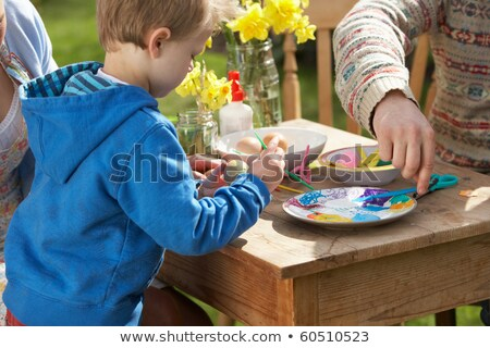 Father And Son Decorating Easter Eggs On Table Outdoors Stock photo © monkey_business