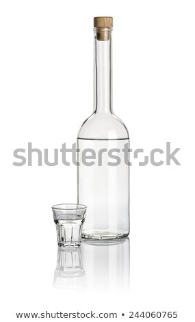 Liquor bottle and beveled shot glass filled with clear liquid Stock photo © Zerbor