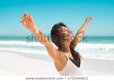 Woman Standing Arms Outstretched On Beach Stock photo © AndreyPopov