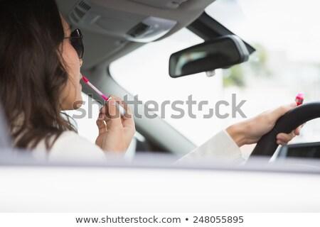 Woman wearing sunglasses using mirror to put on lip gloss Stock photo © wavebreak_media