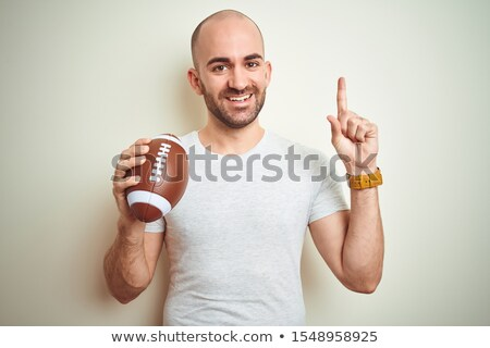 Portrait of smiling American football player holding ball and helmet Stock photo © wavebreak_media