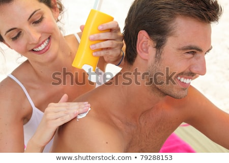 Woman applying sunscreen lotion on mans back Stock photo © wavebreak_media
