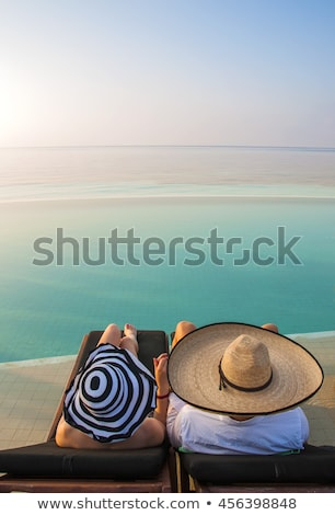 young couple on sun loungers holding hands stock photo © is2