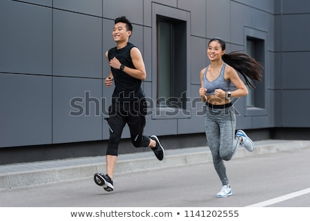 Handsome man and beautiful woman jogging together on street betw Stock photo © boggy