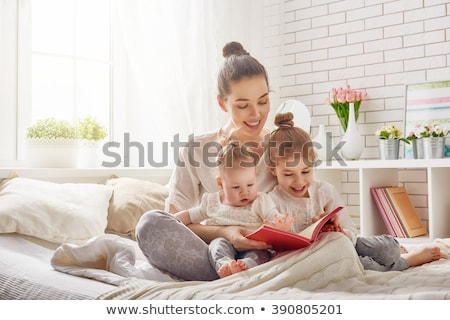 little girls or sisters reading book in bed Stock photo © dolgachov
