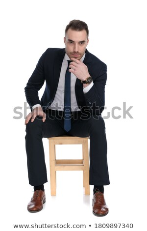 Elegant man  seating, holdiing a hand at his chin Stock photo © feedough