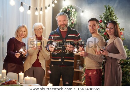 Cheerful family members with sparkling bengal lights enjoying Christmas party Stock photo © pressmaster