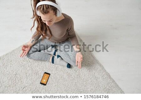 Kilátás derűs fiatal nő fejhallgató ül póz Stock fotó © pressmaster