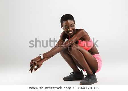 Image of laughing african american sportswoman using wireless earbuds Stock photo © deandrobot