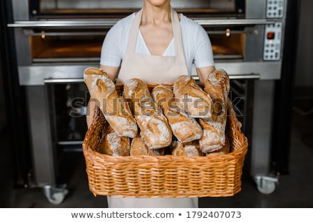 Bakery worker holding basket of bread Stock photo © photography33