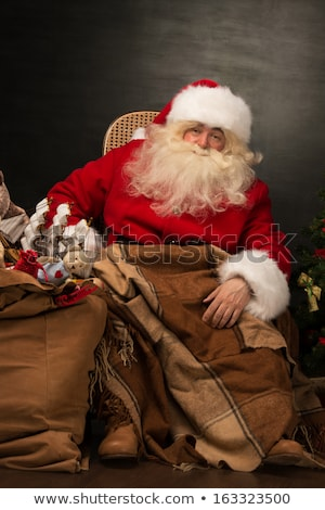 Stockfoto: Santa Sitting In Rocking Chair Near Christmas Tree And Warming H