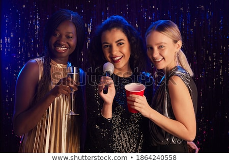 Stockfoto: Three Smiling Women Dancing And Singing Karaoke