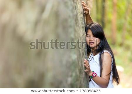 Young Thai girl holding onto a rock Stock photo © smithore